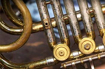 Close up of keys on brass instrument.