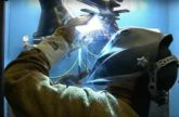 Student wearing welding mask while working.