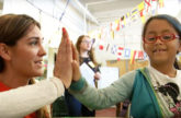Teacher high five-ing with a young student.
