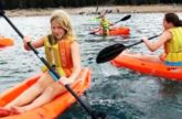 Students kayaking in the water at summer camp.