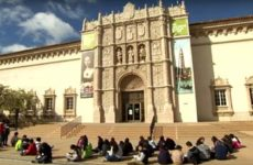Students sitting outside of a museum.
