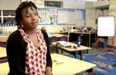 Elementary school teacher sitting in classroom.