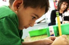 Young student in Transitional Kindergarten class writing.