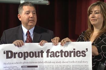 Two school administrators holding a large newspaper article.