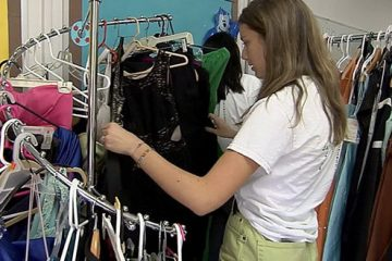 student sorting through clothes at thrift store