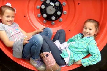 two elementary school students sitting in rim of large tractor tire
