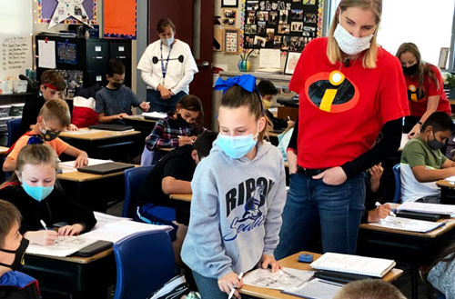 teacher with students in classroom during coronavirus pandemic