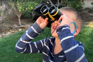 young child looking through binoculars